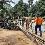 Pasukan Gabungan TNI terlihat membangun jembatan sementara yang rusak akibat banjir bandang di Labura, kemarin.