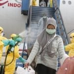 Petugas medis menyemprotkan cairan disinfektan pada Warga Negara Indonesia (WNI) dari Wuhan, China setibanya di Bandara Hang Nadim, Batam, Kepulauan Riau, Minggu (2/2/2020). (ANTARA FOTO/Kementerian Luar Negeri RI/mrh/aww)