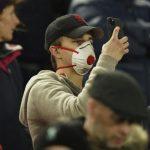 Fans Liverpool menggunakan masker saat menyaksikan laga di Anfield Stadium.(sumber: CNN)