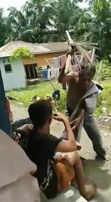 Terlihat seorang warga memukul bocah pemulung