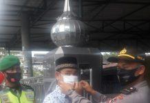 Salah seorang siswa Stukpa yang mengikuti latihan kerja di Polsek Siantar Martoba, Franky M Chandra Ritonga memakaikan masker kepada warga yang akan beribadah di masjid, Jumat (11/9/2020).