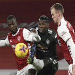 Gelandang MU, Paul Pogba dijepit pemain Arsenal. Laga ini berakhir imbang tanpa gol.